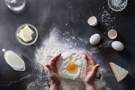 Woman's hands knead dough on table with flour, eggs and ingridients. Top view.