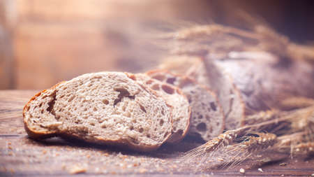 Bread and wheat on wooden table, shallow DOF, raw image