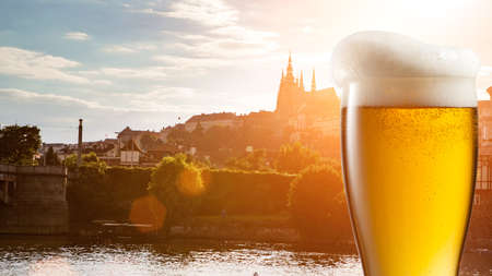 Glass of beer against view of the St. Vitus Cathedral in Prague. Header for website