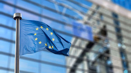 Bandeiras da União Europeia na frente do turva Parlamento Europeu em Bruxelas, Bélgica
