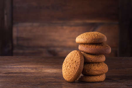 biscuits: pile of oat cookies on wooden table Stock Photo