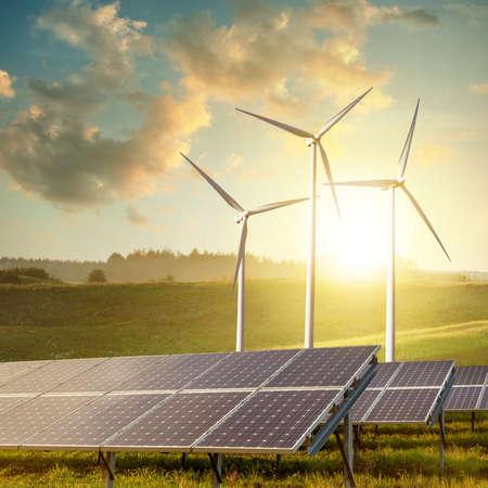 solar panels and wind turbines on sunset summer landscape