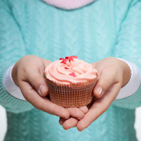vanilla cupcake: Young woman holding a pink cupcake decorated with hearts, isolated on white background