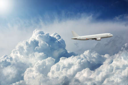 wide open spaces: Plane flying in the sky through dramatic storm clouds Stock Photo