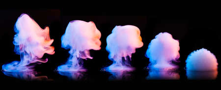 Different color smoke explosions isolated on black background Imagens
