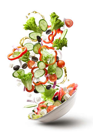 flying salad isolated on white background. Greek salad: red tomatoes, pepper, cheese, lettuce, cucumber, olives and olive oil Standard-Bild