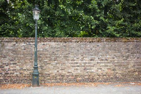 Lamp post strada a sinistra sulla base di muro di mattoni Archivio Fotografico