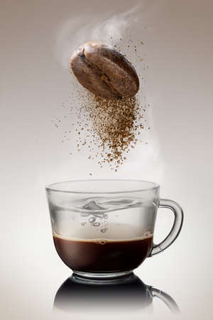 Ground coffee from bean falling into cup with hot water Stockfoto