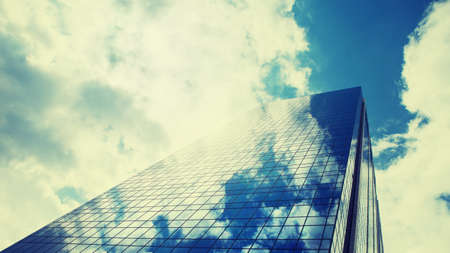 verticals: Reflection of the sky and clouds in glass modern windows of skyscrapper