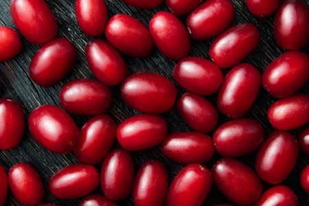 beauteous: food background of close-up Dogwood red berries shooted from above on black wood