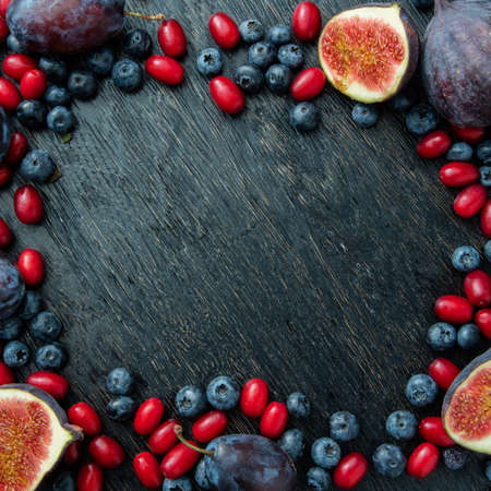 purple fig: Frame made of fresh organic figs, dogwood, blueberries and plums on black wood background. Frame with copy space.