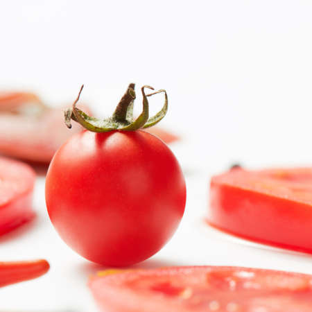 Tomato with green tail and sliced tomato rings on a white background