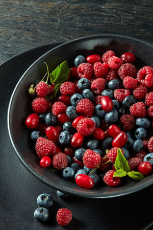 Ceramic plate of assortment berries at dark wooden table. Close up, top view, Standard-Bild