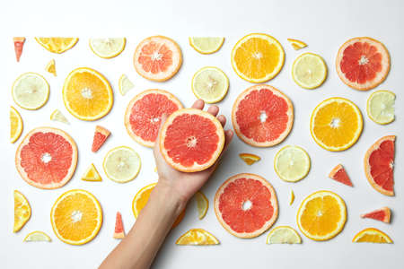 lemon slice: Mix fresh sliced orange, lemon and grapefruit on white background. Female hand putting slice grapefruit, Behind the scenes.