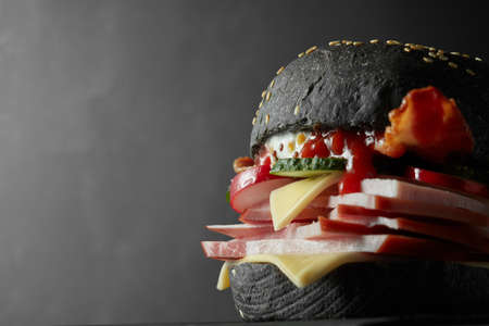 ghoulish: Japanese Black Burger with Cheese. Cheeseburger from Japan with black bun on black background Stock Photo