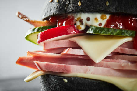 ghoulish: Burger with ham and black bun, with lettuce and mayonnaise and ketchup on white background. Macro Stock Photo