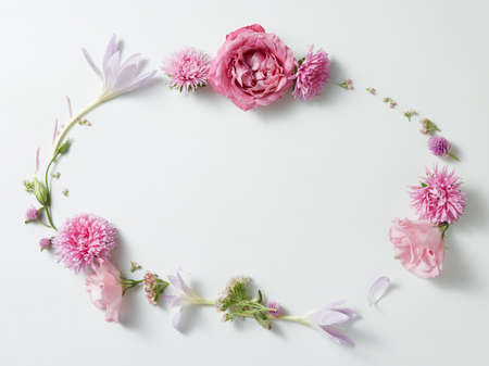 round frame wreath pattern with pink roses buds, branches and leaves with space for text isolated on white background. top view