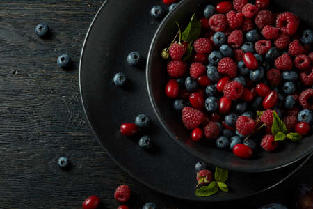 black berry: black plate with healthy berries on a dark background
