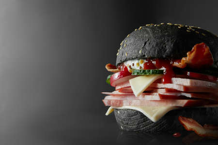 ghoulish: Cheeseburger from Japan with black bun on black background Stock Photo