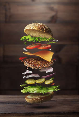 Classic burger ingredients flying on a wooden brown background