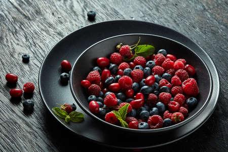 black berry: fresh berries in a black ceramic bowl on black background