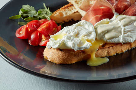 benedict: Poached egg on a piece of bread with salad, becon and tomato on the table Stock Photo