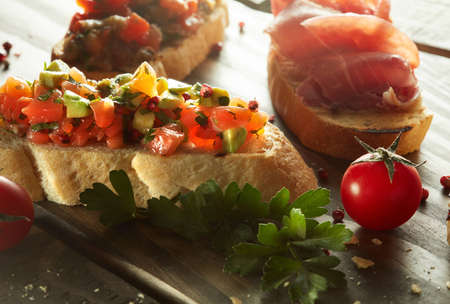 appetizers: Plate of assorted Italian appetizer bruschetta with chopped vegetables, salmon and meat on ciabatta bread, garnished with green herb