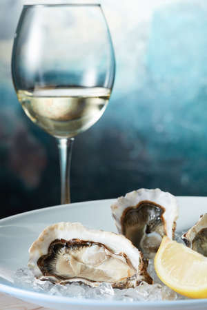 SPARKLING WINE: Raw fresh oyster shellfish with lemon in white plate with wine - seafood style Stock Photo