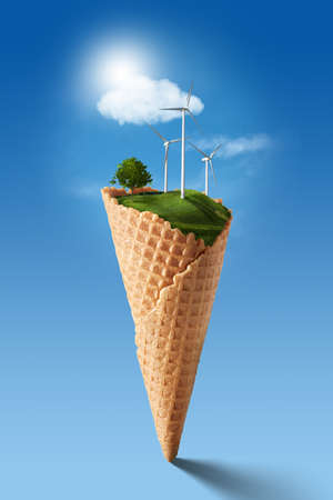 Wind turbines on meadow with tree holds in waffle cone against blue sky and clouds. Green energy concept Stock Photo