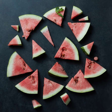 unprocessed: Background of fresh ripe watermelon slices on black Stock Photo