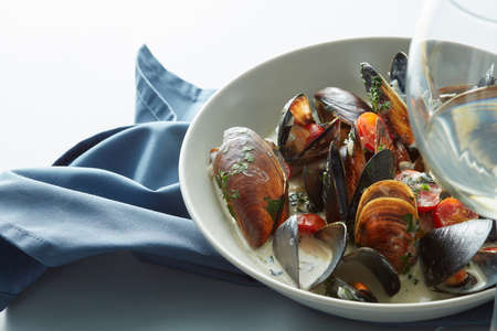 Mussel with white wine sauce and french frie on a plate.