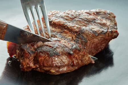 piece of steak cut with a fork and knife on dark background Stockfoto
