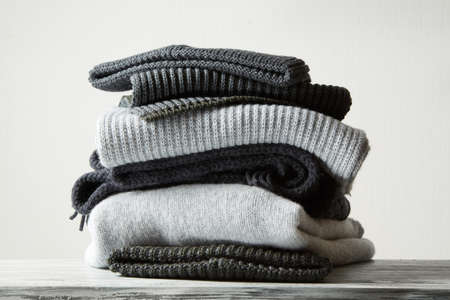 warm cloth: Pile of knitted winter clothes on background, sweaters, knitwear,
