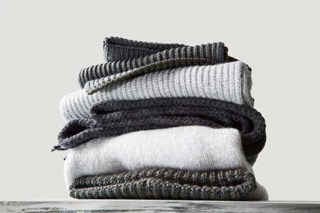 A stack of warm winter knitted sweaters on a white background Stock Photo