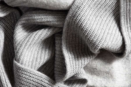 close knit: Textile knitted background. large folds on the warm knit grey scarf.