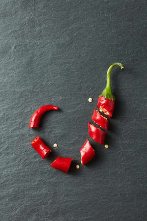 hotness: Chopped red chilli pepper over black concrete background