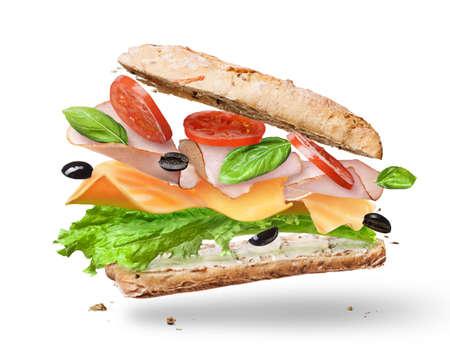 양상추, 토마토, 햄, 치즈가 들어간 Ciabatta 샌드위치가 공중에서 날아 다니는 반으로 절단되었습니다.