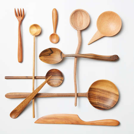 cooking implement: Wooden spoon and knife on a white background
