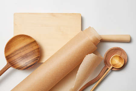 roll baking paper and various wooden spoons on a white background