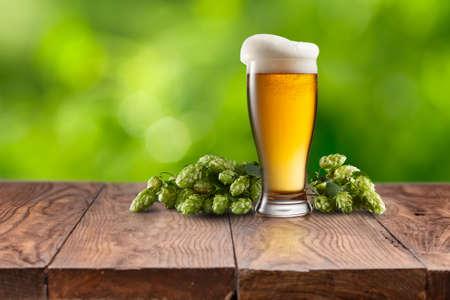 vida natural: Naturaleza muerta con un barril de cerveza y lúpulo en una mesa de madera vacía contra el fondo verde natural