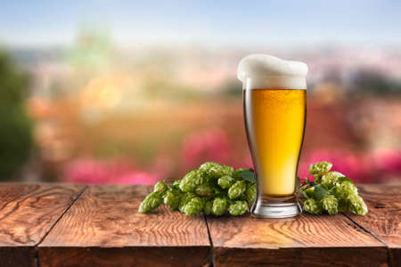 unbottled: glass with Beer with hop on a wooden table on a background of nature
