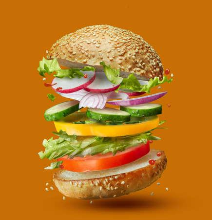 Burger preparation ingredients falling into place isolated on orange Foto de archivo