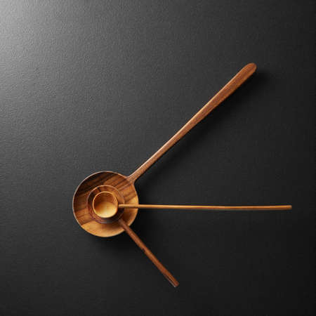 snack time: Top view of black alarm clock with wooden spoons on a black background - concept and idea
