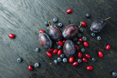 ciruela pasa: Fresh plums and berries on a dark wooden table