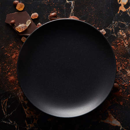 Empty black plate on a dark marble background. Aerial view, with copy space.