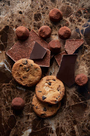 biscuits: Chocolate chip cookies and different chocolate on cocoa powder and dark marble background