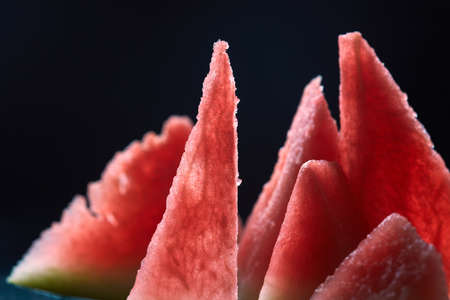 triangle shaped: Triangle shaped watermelon slices on dark grungy background . Top view.