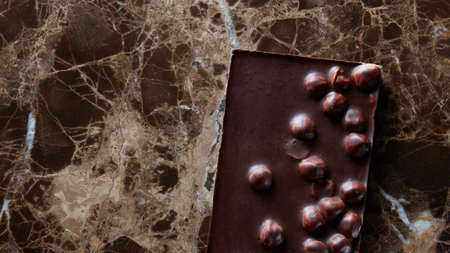cafe bombon: chocolate bar with nuts on a dark marble table