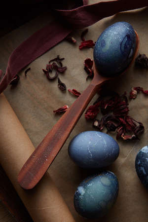blue petals: Wooden spoon with blue egg on parchment with dry petals Stock Photo