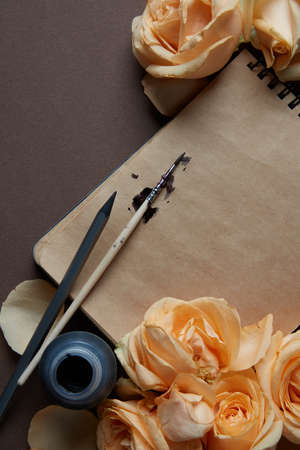 laying forward: Closeup of diary or notebook covered by orange roses for your notes. flat lay Stock Photo